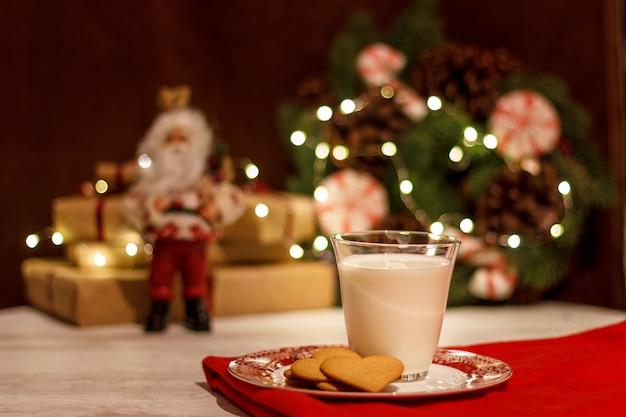 Пряники и стакан молока для деда мороза на фоне рождественской гирлянды и венка из хвои