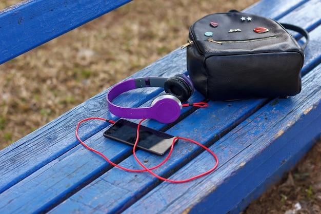 青い公園のベンチにスマートフォンと黒のバックパックを備えたヘッドフォン