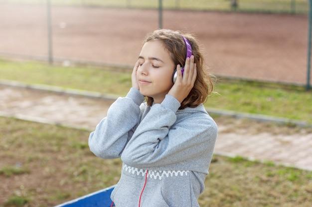 若い美しいファッショナブルなティーンエイジャーの女の子は、スマートフォンからヘッドフォンで音楽を聴きます