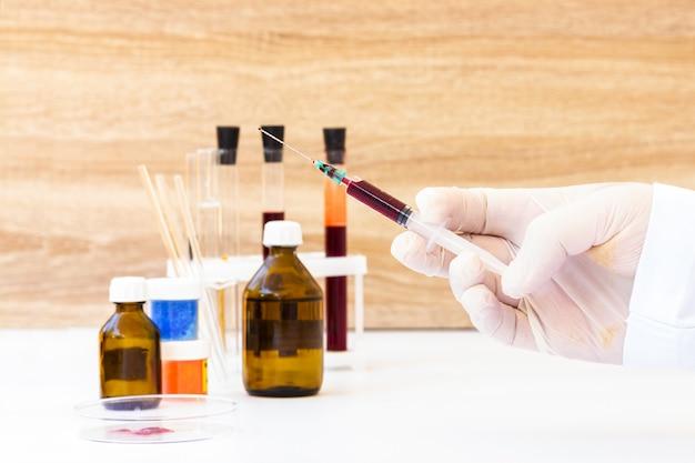 Кровь в шприце. лаборатория для сдачи анализов крови. тест на короновирус