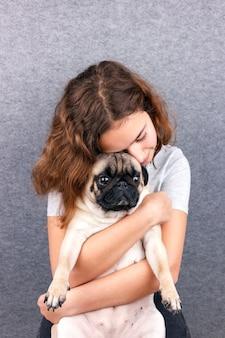 Любимая любовь. кудрявая девушка-подросток с любовью обнимает свою грустную собачку