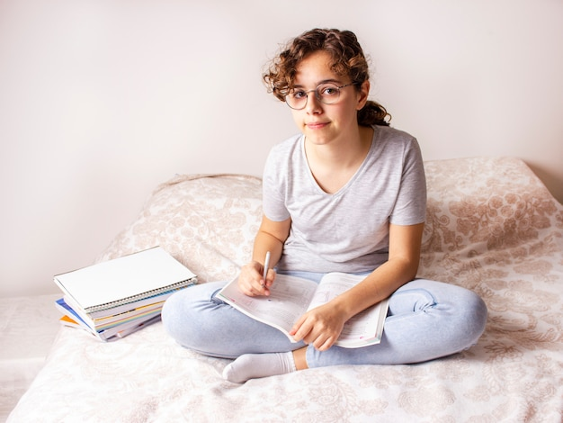 Девочка-подросток на кровати учится дома из-за карантина