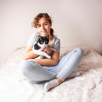Красивая кудрявая девушка-подросток в постели обнимает свою кошку