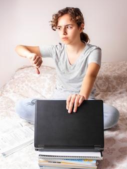 Несчастная девочка-подросток с большим пальцем вниз на онлайн-образование