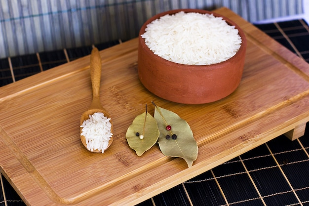 粘土のボウルと木製のスプーンの白米。ベイ葉と
