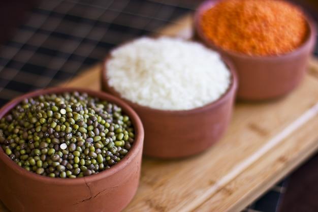 白い米、赤いレンズ豆と木のトレイ上の緑のエンドウ豆。