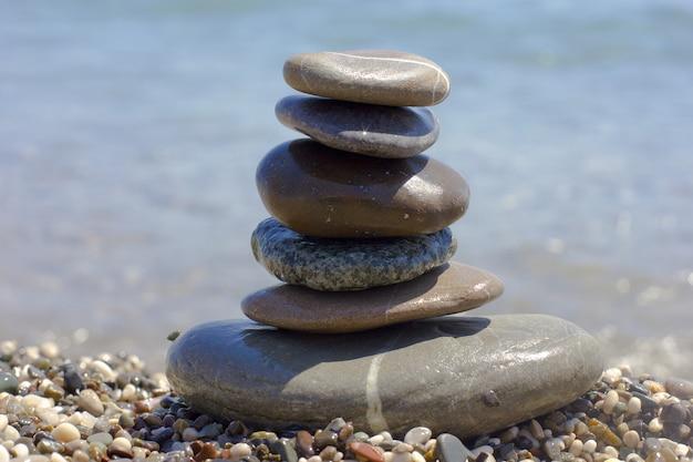 青い海の海岸の小石のピラミッド
