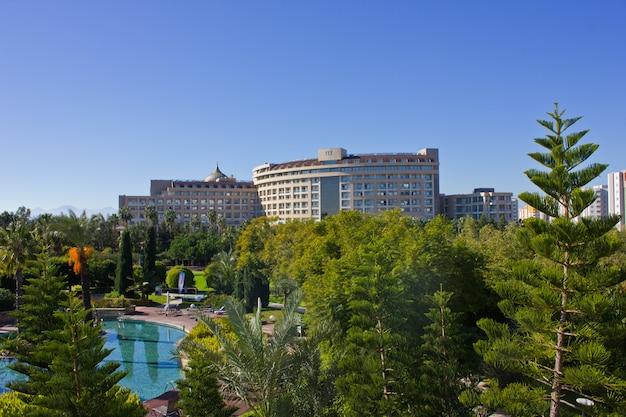 Вид на отель у бассейнов, моря, пальм и шезлонгов