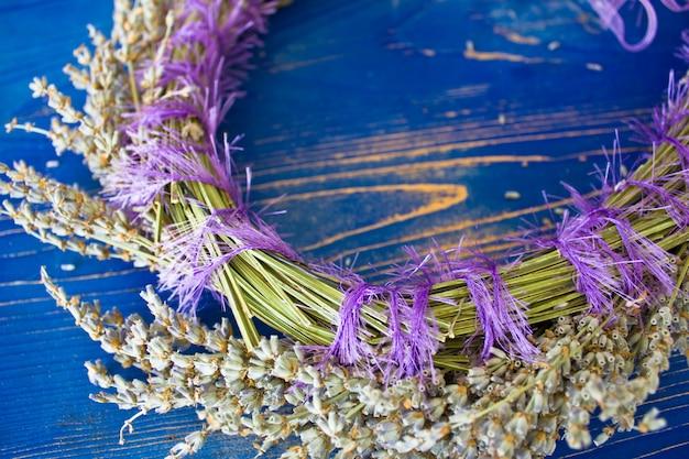 青い木製のボード上にラベンダーの花輪