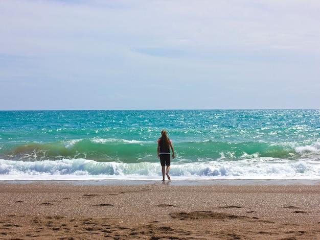 若い女の子が青い海の近くのビーチに立つ