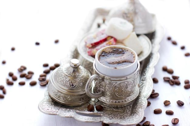 トルコのコーヒー、伝統的なトルコのお菓子と銀マグ