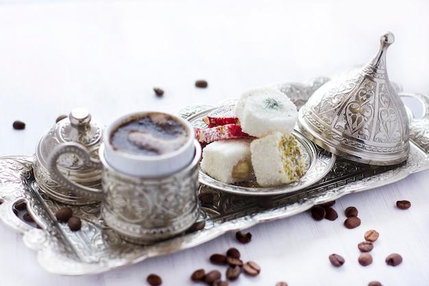 Турецкий кофе с традиционными турецкими конфетами в серебряной кружке. селективный фокус.