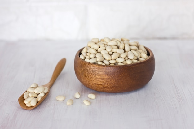 木製のボウルと白いテーブルの上のスプーンで生の白豆