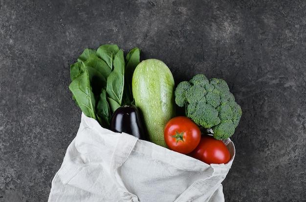 暗いスレートテーブルの上の繭の再使用可能なバッグのビーガン野菜。廃棄物ゼロ、ケア、健康の概念