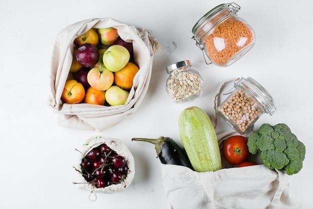 ゼロ廃棄物食品貯蔵エコバッグトップビュー。新鮮な野菜、フルーツが入った再利用可能なコットンバッグ