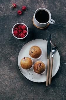 ブラックコーヒーとラズベリーのマフィン濃いコンクリートのテーブルの上の皿の上のカップ。上面図