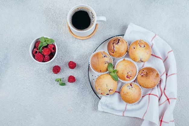 おいしい朝食用食品のコンセプトです。軽いコンクリートの上にコーヒー、ラズベリーのマフィン。上面図