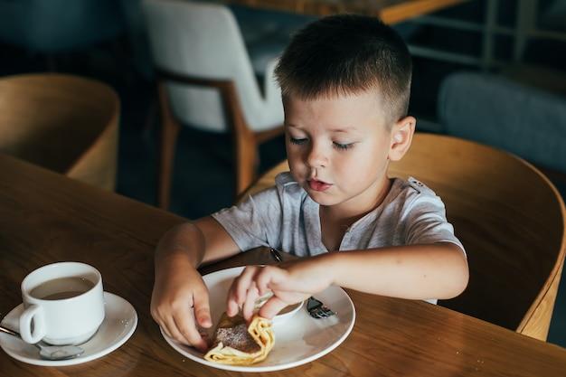 カフェで朝食を持っている小さなかわいい男の子。