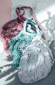 Две многоразовые хлопчатобумажные сумки (сетчатые сумки) трехцветного цвета с теневыми туфлями. эко дружественных