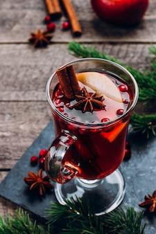 ホリデーホットドリンク。木製テーブルの上のスパイスとリンゴとガラスのホットワイン