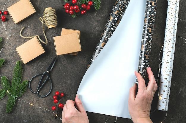 Женская рука упаковывает рождественские подарки, подарочные коробки и украшает на темном