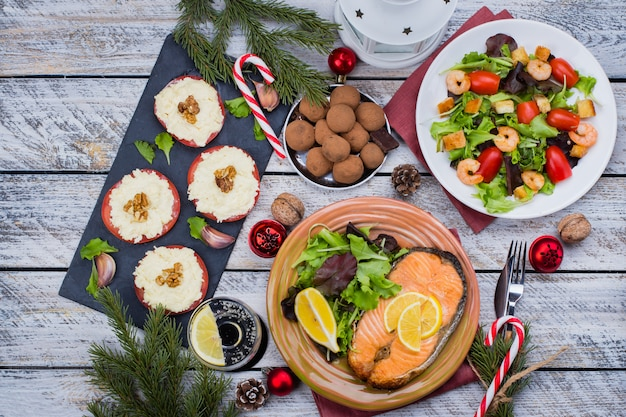 クリスマスや新年の家族との夕食は、休日の装飾とテーブルコンセプトを設定します。白い木製のおいしいローストステーキサーモン、サラダ、前菜、デザート。上面図
