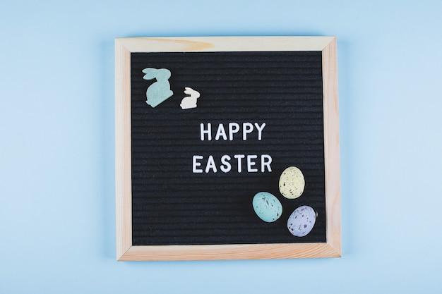 イースターカードフラットレイアウトコンセプト。テキストハッピーイースターとパステルカラーのカラフルな卵、青い背景に木製のウサギのグリーティングボード。上面図。