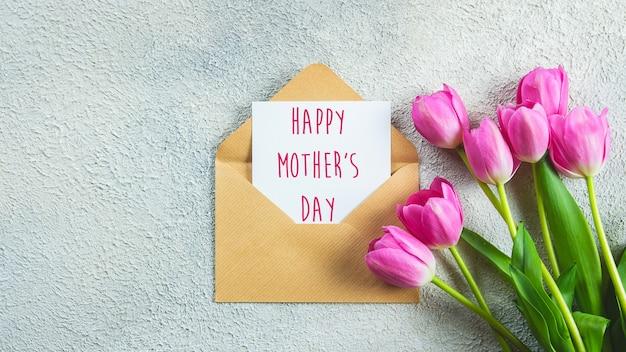 母の日カード。ピンクのチューリップの花とコンクリートの背景にテキスト付きのカード。フラット横たわっていた、トップビュー。バナー
