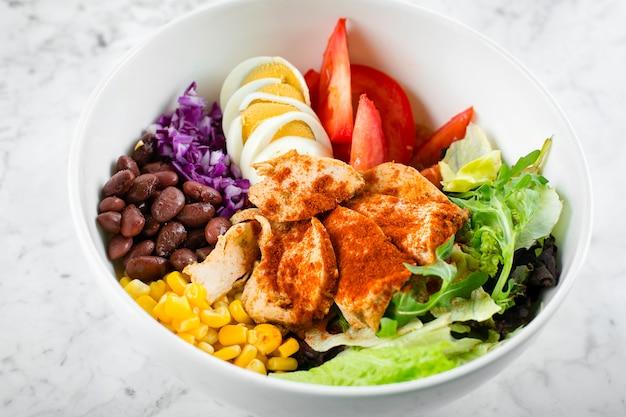 健康食品のコンセプトです。チキン、卵、トマト、レタス、トウモロコシ、小豆、赤キャベツのランチボウル。きれいな食品とダイエット栄養の概念。閉じる