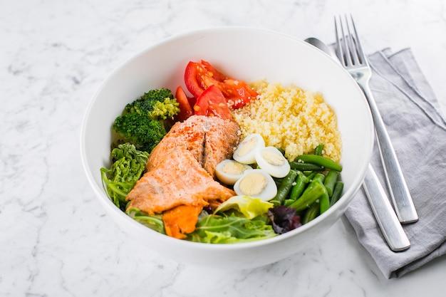 健康的な食事、ケト食品のコンセプト。大理石のテーブルに魚のサラダボウル。サーモン、クスクス、野菜、ウズラの卵のサラダ。トップビュー、コピースペース