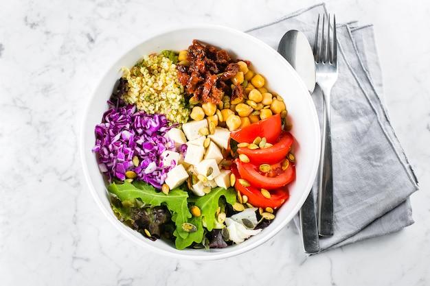 Вегетарианская, здоровая, детокс еда концепции. вегетарианская чаша будды. сырые овощи, тофу и булгур в белый шар со столовыми приборами. вид сверху