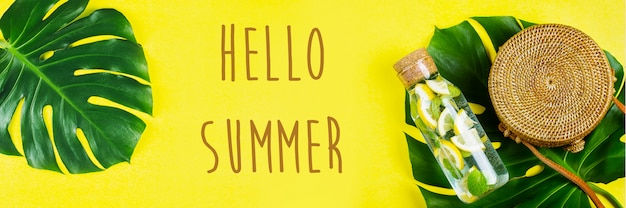 Привет лето баннер для сайта. круглая сумка из ротанга и стеклянная бутылка с лимонадом и листом монстеры. желтый, солнечный фон. плоская планировка, вид сверху