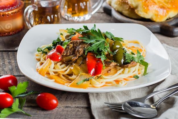 野菜と素朴な木製のテーブルに肉と伝統的なアジアのウズベキスタンラーメン。閉じる