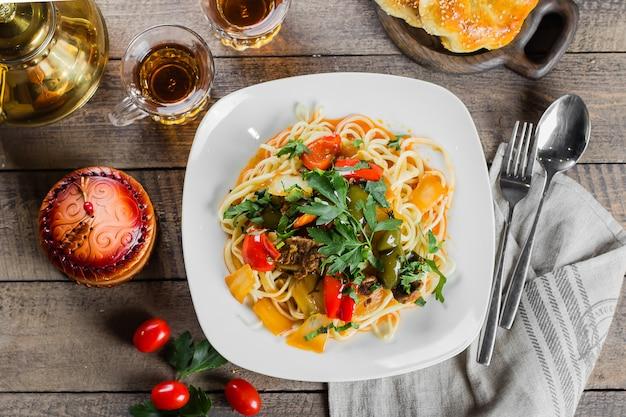 野菜と素朴な木製のテーブルに肉と伝統的なアジアのウズベキスタンラーメン。上面図