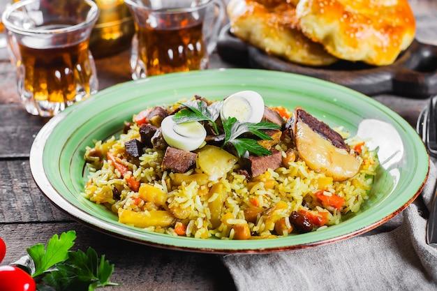 肉と木製のテーブルにご飯と国立伝統的なウズベキスタンのピラフ。東洋料理のコンセプトです。クローズアップ画像