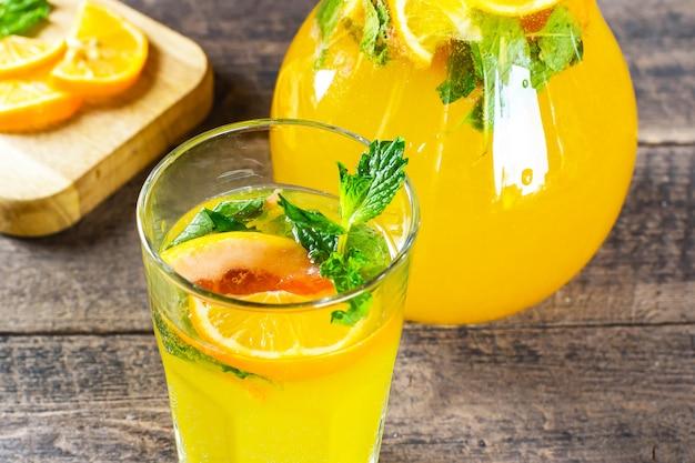 オレンジ、グレープフルーツ、ミントと素朴な木製のテーブルの上のガラスの夏の柑橘類のレモネード