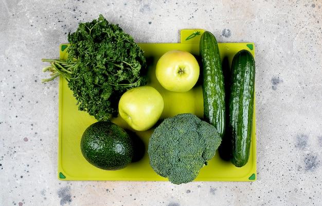 健康的なビーガンフードダイエットのコンセプトです。緑の野菜と果物のコンクリートのテーブルに緑のまな板。平面図、フラットレイアウト。料理のコンセプトです。
