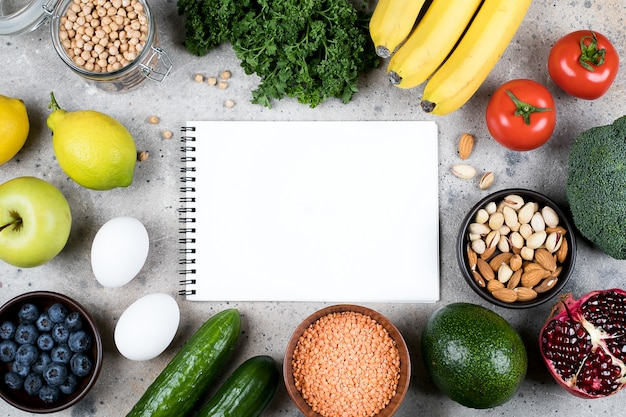 Концепция рецепта пищи макет. зеленые овощи, помидоры, орехи, фрукты, чечевица, нут, зелень и пустой блокнот на сером бетонном столе. плоская планировка, вид сверху, копия пространства