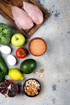 食品栄養コンセプト。石のテーブルに肉、野菜、果物、豆製品。トップビュー、フラットレイアウト、コピースペース
