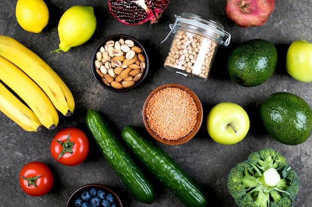 健康的なビーガンフードダイエットのコンセプトです。緑の野菜、トマト、ナッツ、暗いコンクリートのテーブルの上の果物。フラット横たわっていた、トップビュー