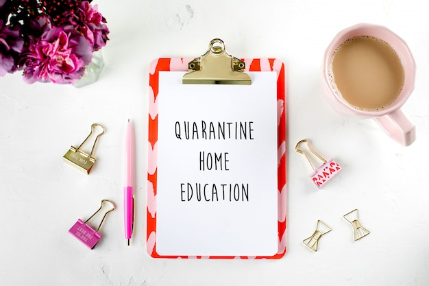 ピンクの花、一杯のコーヒー、クリップボード、ペン、クリップとファッションの女性的なホームオフィスのワークスペース。平面図、フラットレイアウト。ホームスクール、オンライン教育、家庭教育、検疫、コロナウイルスのコンセプト