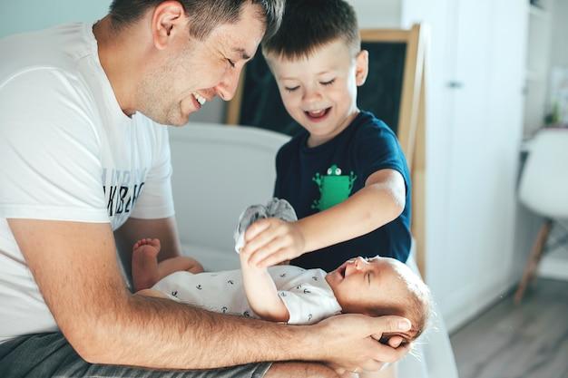 かわいい新生児を抱き締める父の手。父と弟と小さな赤ちゃん。