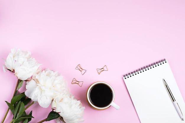 コーヒーのマグカップ、ノートブックを空にし、ピンクのテーブル背景に白い牡丹の花。トップビュー、フラットレイアウト、コピースペース