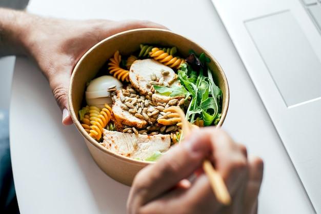 男の手でヘルシーなランチボウルを食べる。ホームオフィス、食品配達、デトックス、食品のコンセプト
