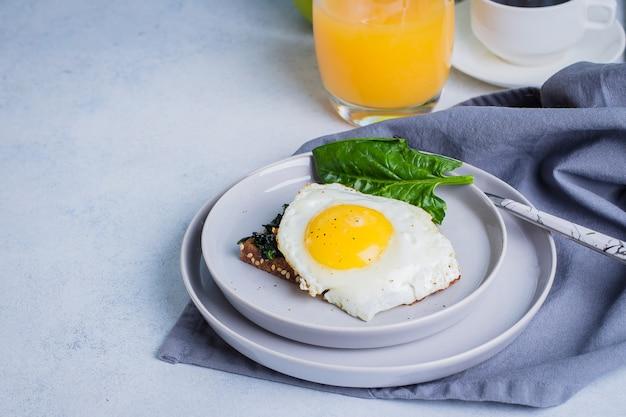 ライ麦パンは、揚げほうれん草と卵の青いテーブルの上で乾杯します。健康的な朝食用食品のコンセプト。