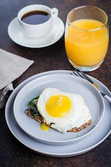 ライ麦パンは揚げほうれん草と卵で乾杯します。健康的な朝食用食品のコンセプト。