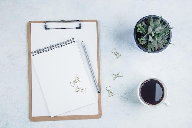 ノート、消耗品、花とコーヒーカップのオフィスデスクテーブル