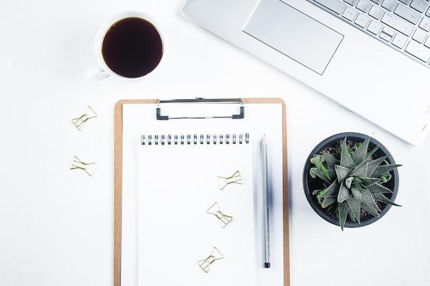 コンピューター、消耗品、ノートブック、花、コーヒーカップを備えたオフィスデスクテーブル