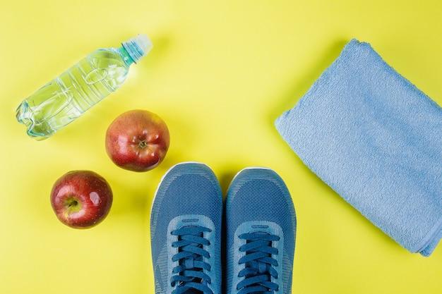 Плоские лежал синие кроссовки, полотенце, красное яблоко и бутылка воды на желтом фоне
