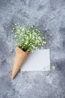 春の最小限の概念。石膏の花を持つワッフルコーン。母の女性の日コンセプト。